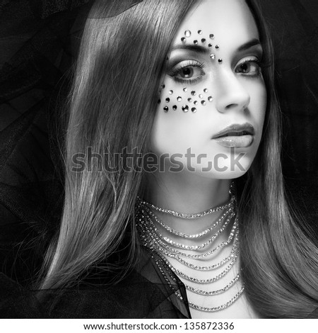 Portrait of sexual beautiful girl with strasses on face, on a dark-grey background