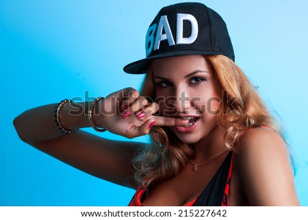 Portrait of sexual seductive female in black hat on blue background in studio - stock photo