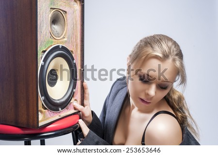 Portrait of Sexy and Seductive Young Caucasian Woman Listening to Loud Speaker. Horizontal Image - stock photo