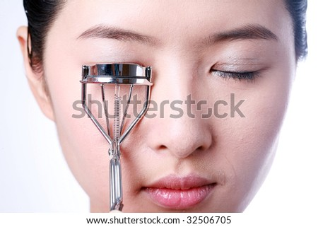 portrait of sexy asian young woman holding eye lash curler - stock photo