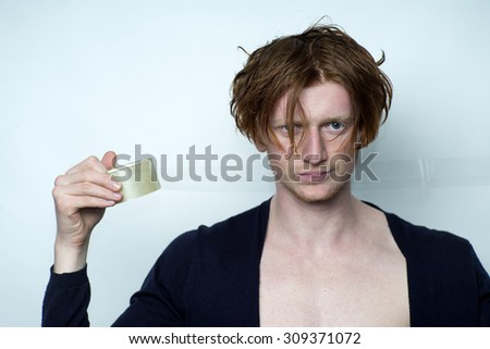 Portrait of sexy attractive young man model with red hair in black jersey with beautiful chest holding scotch tape looking forward standing in studio on white background copyspace, horizontal picture - stock photo