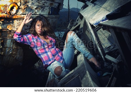 portrait of sexy blond woman in jeans posing in from of shipwreck