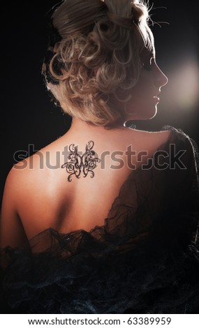 portrait of sexy blonde with tattoo on her back - stock photo