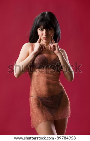 Portrait of sexy brunette in lingerie and shiny mesh dress on red background in studio - stock photo