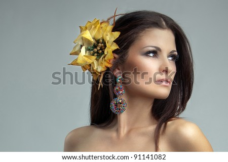 portrait of sexy brunette with a yellow flower in her hair close-up - stock photo