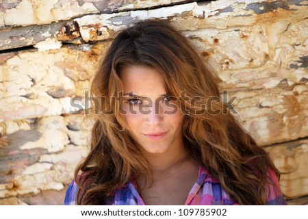 portrait of sexy brunette woman posing in from of shipwreck - stock photo
