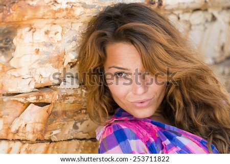 portrait of sexy brunette woman posing in front of shipwreck - stock photo