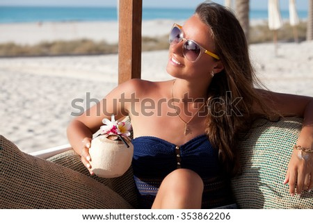 Portrait of sexy cheerful woman with exotic cocktail relaxing at the luxury beach. Girl at travel spa resort. Summer luxury vacation. - stock photo