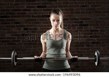 Portrait of sexy fit woman lifting dumbbells on brick background  - stock photo