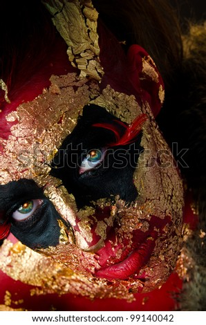 Portrait of sexy girl with heavy gold and red demon makeup - stock photo