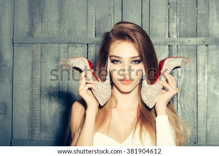 Portrait of sexy glamour fashion young girl with long beautiful hair holding shoes in hands near face with tongue on wooden background, horizontal picture - stock photo