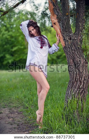 Portrait of sexy, lovely young girl in a beautiful national shirt standing next to a tree in an outdoor