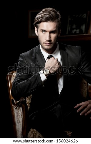 portrait of sexy macho man over dark background wearing a chronograph wrist watch - stock photo