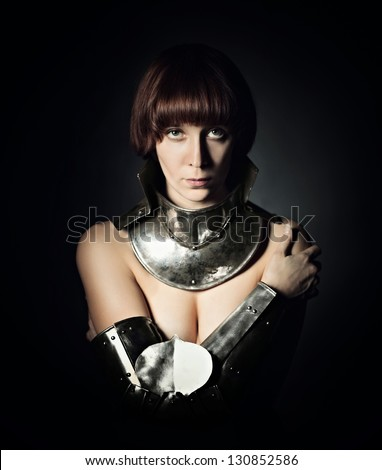 Portrait of sexy medieval female knight in armour over black background - stock photo