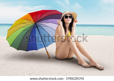 Portrait of sexy model with colorful umbrella at beach