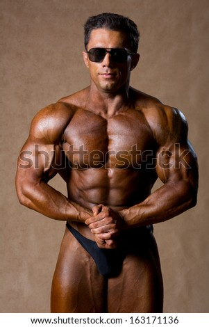 Portrait of sexy muscle man posing in studio. Bodybuilder with sunglasses
