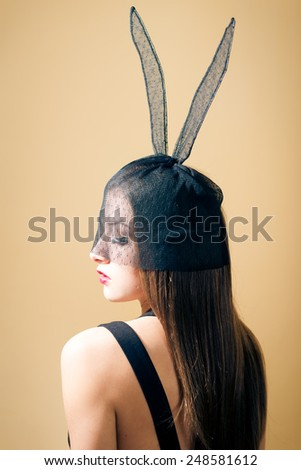 Portrait of sexy mysterious young pretty lady and bunny ears mask - stock photo
