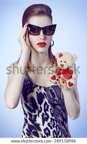 Portrait of Sexy redhead woman in trendy mini dress holds loving teddy bear with red heart on blue background. Seductive lady in sunglasses, sensual lips. Provocative young girl in playful flirty mood - stock photo