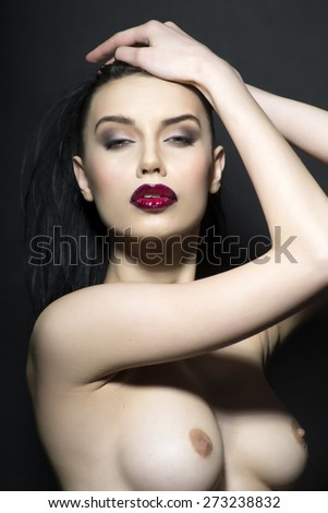 Portrait of sexy stripped white-skinned brunette with beautiful breast looking forward, vertical picture - stock photo