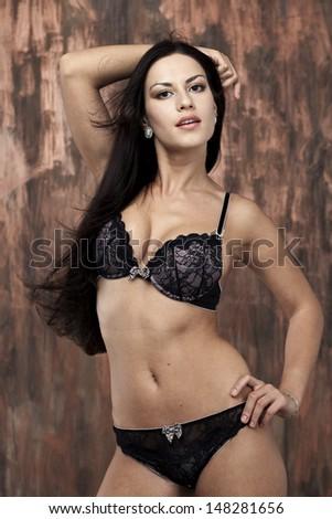Portrait of sexy woman in black underwear on a dark wall - stock photo