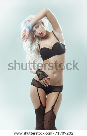 portrait of sexy woman posing in black lingerie over pastel turquoise - stock photo