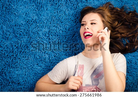 Portrait of sexy young beautiful woman relaxing over blue copy space and talking on mobile phone - stock photo