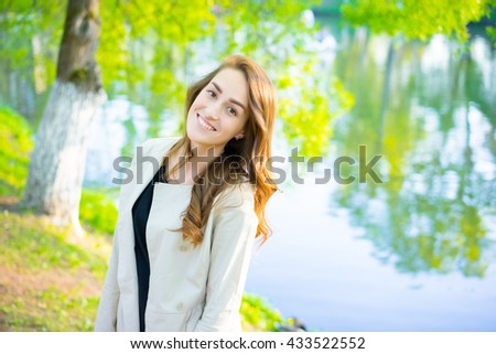 Portrait of sexy young business woman smiling and looking to camera with lake on blurred background in the park.
