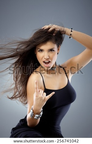 Portrait of sexy young provocative girl showing rock on hand gesture, shouting. - stock photo