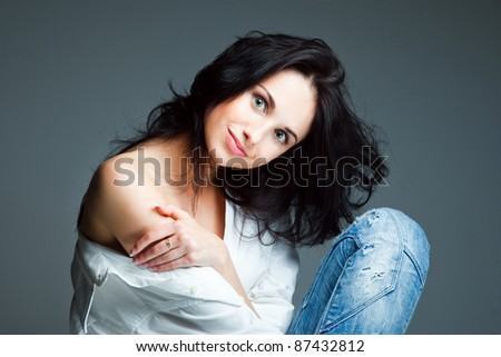 Portrait of sexy young woman on wearing blue jeans on gray background - stock photo