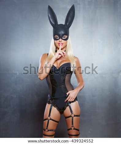 portrait of sexy young woman posing in rabbit mask and bodysuit doing shh gesture against steel wall