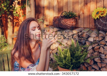 Portrait of sexy young woman sitting on a wooden chair in the garden - stock photo