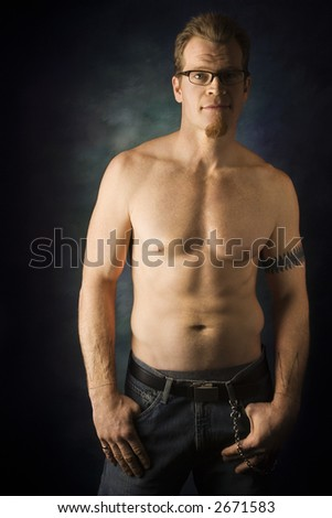 Portrait of shirtless adult Caucasian man on studio background looking at viewer.