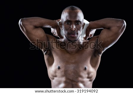 Portrait of shirtless athlete holding rugby ball behind head standing against black background