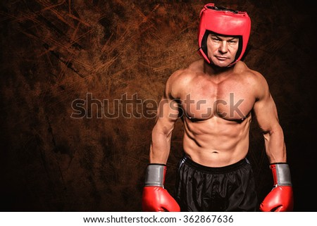 Portrait of shirtless man with boxing headgear and gloves against dark fence - stock photo
