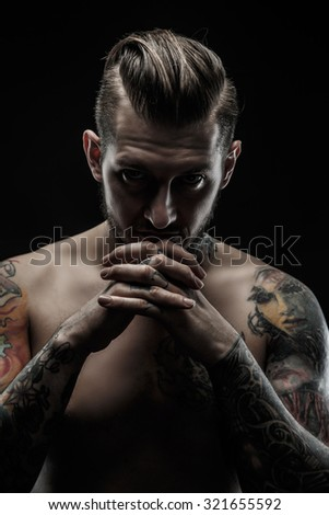 Portrait of shirtless man with tatooed body. Isolated on black background.