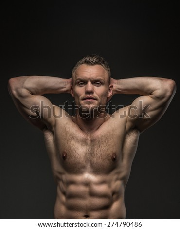 Portrait of shirtless muscular guy isolated on grey background - stock photo