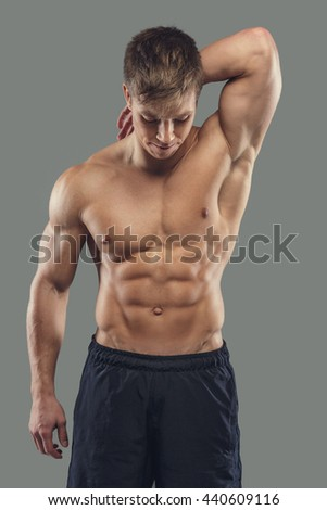 Portrait of shirtless muscular male isolated on a grey background.