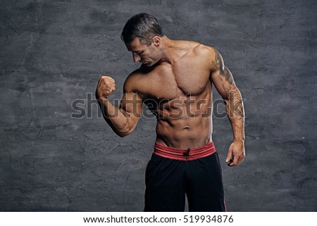 Portrait of shirtless muscular middle age male isolated with illumination on grey background.