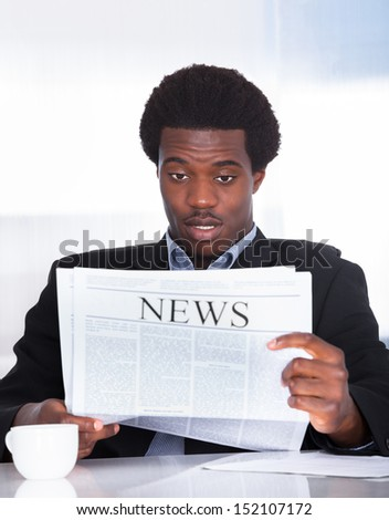 Portrait Of Shocked Businessman Reading Newspaper In Office