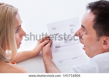 Portrait of shocked couple after looking at bill - stock photo