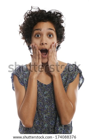 portrait of shocked hispanic girl with mouth open and hands on face, looking at camera on white background
