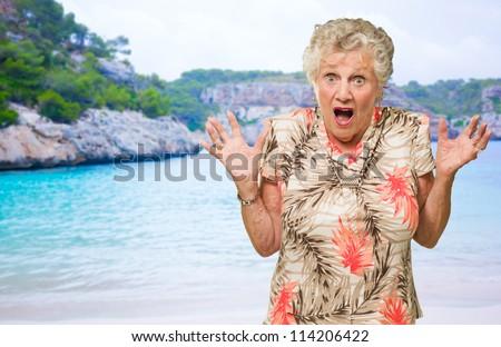 Portrait Of Shocked Senior Woman On Beach - stock photo
