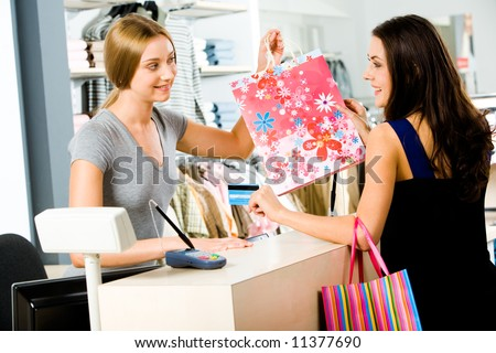 Portrait of shop assistant giving  bag to happy woman - stock photo