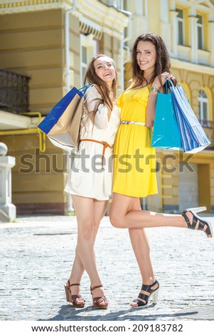 Portrait of shopaholics. Two girlfriends holding shopping bags and walk around the shops. Smiling girlfriends having fun together walking on the street