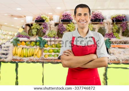portrait of shopman at the fruits store with crossing arms - stock photo