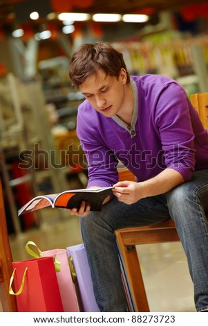 Portrait of shopper looking through magazine with paperbags near by - stock photo