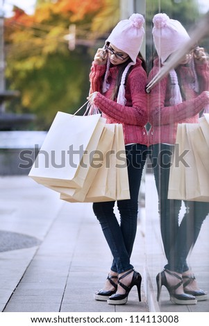 Portrait of shopping woman with bags talking on the phone. shot outdoor