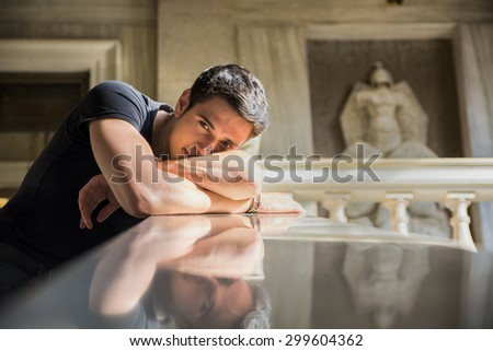 Portrait of Shy Attractive Young Man Leaning on Folded Arms Against Polished Marble Staircase Railing Inside Classical Building - stock photo