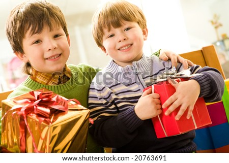 Portrait of siblings holding presents while in supermarket - stock photo