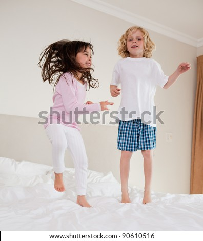 Portrait of siblings jumping on a bed - stock photo